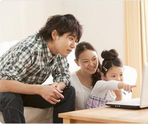 家族でパソコンを見る写真